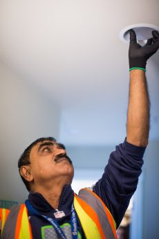 ECOSS staff installing energy efficient light bulb